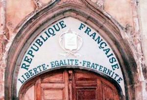 Tympan d'une église (Aups, Var) avec la devise de l'état français datant de 1905 apposée pour signifier que l'église appartient à l'État. Source : Wikimedia Commons